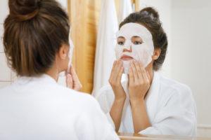 Lipstick effect tijdens de coronacrisis. In plaats van lipstick breng vrouw thuis een sheet masker op haar gezicht aan.